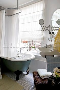 Bathroom with old fashioned shower rail above freestanding bath in