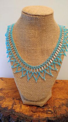 This Necklace is made with seed beads so it is very soft as it lays around the neckline. It's made with soft blue beads and is 18in long.