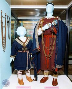 Museum display of the 11th century outfits of woman and child. In this one the woman wears a red wool peplum dress with several long chains suspended from brooches.