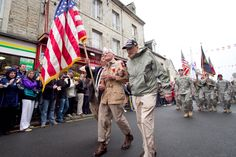 Zane Schlemmer, a veteran U.S. Army paratrooper who jumped into northern France as a sergeant with the 82nd Airborne Division, walks in his jump boots down the main street of Sainte-Mère-Église, France, with other World War II veterans during the 67th anniversary of the Allied invasion of France, June 5. French citizens applaud as he and current paratroopers with the 82nd and other Army units parade past. Photo by Sgt. Michael J. MacLeod