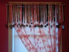 Sports medals hung on a curtain rod as a valance.