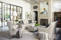 The family  room's 20-foot iron doors (which boast a paned dog door), bring in streams of natural light and open onto the patio. Plush Lee Industries sofas offer guests cozy seating. Painting through Huff Harrington Fine Art.