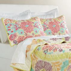 Hand quilted of 100% cotton, our exclusive quilt has a uniquely artistic pattern with an almost hand-drawn look and feel. It features an oversized floral medallion in fuchsia, green, blue, purple and orange tones and the same print on the reverse for a sophisticated, versatile look.