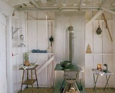 Shack with exposed framing, corrugated metal hearth.