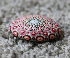 Mandala steen met onder andere rode en roze tinten. Circa 6 cm diameter om een indruk van de grootte te geven. De steen is 90 gram. De mandala stenen zijn afgewerkt met een laagje vernis maar kan alsnog niet gebruikt worden voor buiten, etc. Elke steen is uniek en uiteraard handgemaakt. Op de achterkant van de mandala steen staat mijn naam. De stenen komen uit Duitsland en Frankrijk. Voor het idee ben ik geïnspireerd door Elspeth McLean. Verpakt in een organza zakje met een leuk label. Leuk…