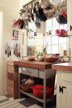 Butcher block island, hanging rack, and amount of light in this kitchen