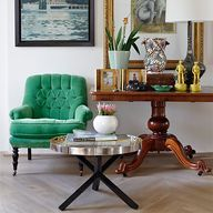 I like the mix of traditional antique table with funkier elements like the velvet chair and coffee stand