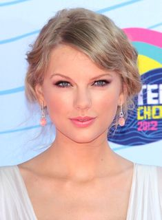 Taylor Swift's Blonde, Romantic, Wavy, Updo Hairstyle and you can kinda see her white dress.