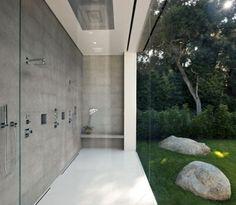 Glassed in shower.  Concrete bathroom contrasted with natural green scenery.  glass pavillion | bathroom ~ steve hermann builder