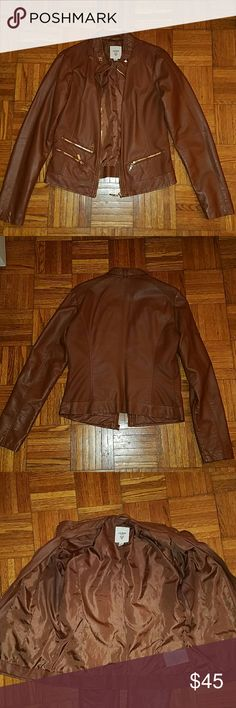 Guess Leather Jacket Please read before you purchase!!!!!  Gorgeous Toffee color jacket with Gold detailing. It has 1 real pocket on the left side and 1 real and false pocket on the right side.   Pay close attention to the 2nd pic it shows a tiny needle size hole on the back of the jacket in the middle.   The 5th pic shows tiny pin holes on the left arm of the jacket.   The 6th pic is a larger pic of the 2nd pic just to show how small it is. Guess  Jackets & Coats