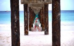 Two tourist walk under a jetty as they stroll along a beach in Bridgetown