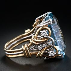 A liquid pastel blue aquamarine weighing 11.00 carats is artfully presented in this bold retro mounting composed of intertwined, two-tone gold wire dotted with ten sparkling round diamonds. A unique and exceptional treasure, circa 1940s -- early 1950s.