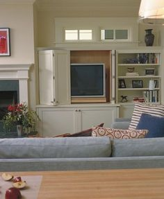 This style keeps the tv hidden while making the fireplace the (rightful) focal point, without having to tilt your head back the way many homes have their tvs above the fireplace.  Nice!