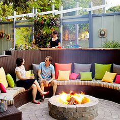 Gather around a firepit wall Overlapping panels of ipe wood and colored concrete flank the firepit in this backyard in Los Altos Hills, California. Stone veneer forms a chimneylike background for the flames, creating a classic focal point for this true outdoor living room. 38 ideas for firepits | Firepit circle sitting area | Sunset.com