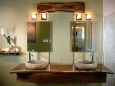 These stone sinks atop a vanity made of natural wood brings a touch of the outdoors to your bathroom, while the wood piece at the top of the glass waterfall ties the look together. See it at diynetwork.com.