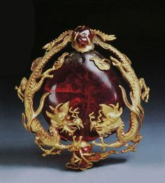 Two dragons presenting a heart-shaped amber, buried between 1647 and 1658. From the tomb of Lady Chen, wife of Tong Bonian, in Dengfushan outside of the Zhonghua gate, Nanjing. Amber and ruby; gold with repoussé and filigree designs.