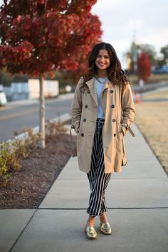 Winter work outfit. How to wear a trenchcoat. Stripey drawstring pants, gold loafers, trenchcoat.
