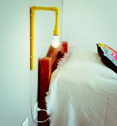 Aposte em ideias criativas para fazer uma luminária de cabeceira, como usar um cano colorido.