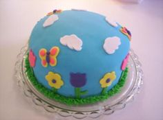 Birthday Butterflies:  This butterfly and flower cake is a 2-layer 8 x 2 chocolate cake. With chocolate fudge icing. I covered it in sky blue colored fondant. I freehanded the