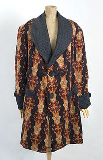 "Gentleman's smoking jacket, 1870s-1880s. Made from printed wool faille and lined with contrasting printed cotton. The front opening is embellished with Brandenburg tape appliqués around the top button. The brilliant print features intricate, exotic Eastern motifs. Although upper class Englishmen would not wear the ethnic clothing favored by artists and bohemians, a plush ""ethnic-style"" smoking jacket was just daring enough for aristocratic taste."