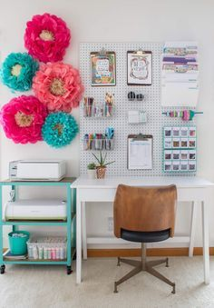 No escritório da blogueira Ann Marie, as grandes estrelas são a placa perfurada (também chamada de pegboard) e as flores de papel que ornamentam a parede. A mesa é simples, por isso é acompanhada também de um carrinho colorido que abriga impressora e materiais.