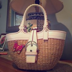 """Coach wicker satchel. In excellent condition. Fun summer bag. 13"""" w x 7"""" h with a 7"""" handle. White leather with pink trim. Pink butterfly accent. Buckle has a magnetic closure. There is one mark on the wicket from use otherwise in excellent condition. Coach Bags Satchels"""