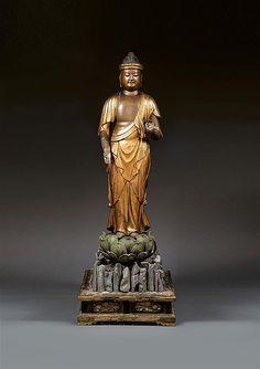 GRANDE SCULPTURE REPRÉSENTANT LE BOUDDHA AMIDA en bois sculpté, laqué et doré, en samabhanga sur un lotus reposant lui-même sur une terrasse en forme de rocher traité au naturel, les mains en vitarkamudra, la tête amovible aux yeux mi-clos en méditation et le chignon à coquilles sommant l'ushnisha. Sur son socle parallélépipédique à décor sculpté et ajouré de fleurs. (Petits accidents et restaurations anciennes). Japon, période Édo, XVIIe-XVIIIe siècles. A LARGE LACQUER SCULPTURE, JAPAN, EDO…