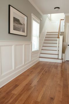 Entrance - White panels and stairs and brown wood flooring