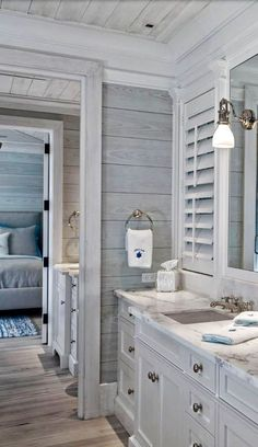 Love the grey wooden shiplap walls, white shutters, and beautiful detailed vanity.