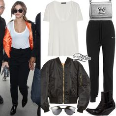 Selena Gomez was spotted arriving at LAX Airport wearing a Bomber Jacket ($1,620.00), Track Pants ($665.00) and Cowboy Ankle Boots ($1,250.00) all by Vetements, The Row Sabeen T- Shirt ($280.00), a Louis Vuitton Twist PM Handbag ($3,250.00) and Dior So Real Sunglasses ($465.00). You can find a similar jacket for less at Boohoo ($35.00).