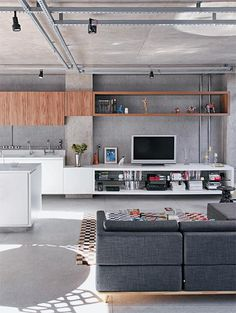Color combinations - warm wood + modern matte white + concrete / Extension of kitchen into TV room - kitchen cabinet and counter materials extend and turn into different, room appropriate storage / Modern / Minimalistic / Industrial