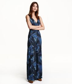 Sleeveless V-neck jumpsuit in jersey with a printed pattern. Opening at back with covered buttons at back of neck, seam at waist, side pockets, and wide, straight legs. Unlined.
