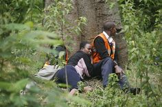 Medics take cover behind a large tree as gunfire and explosions are heard