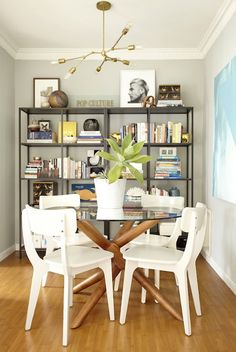Chic dining room with gray paint framing pair of Ikea Vittsjo Shelving Units filled to the brim with collectibles and books. Benjamin Moore Half Moon Crest Lon walls. indsey Adelman style chandelier over West Elm John Vogel Table surrounded by West Elm Klismos Dining Chairs -