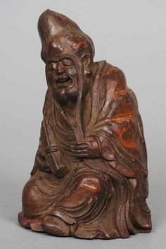 A Chinese carved bamboo figure of a sage Modelled seated, holding a scroll. 16.5 cm high.