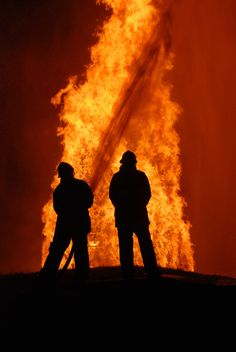 Two firemen battling against raging fire, NOTE: top left corner particles are from fire and water spray, not camera noise Stock Image Firefighter Emt, Firefighter Pictures, Wildland Firefighter, Fire Dept, Fire Department, Fire Tornado, Fire Prevention, Water Spray, Dark Skies
