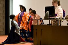 A woman being dressed in junihitoe, layer by layer, at a kimono demonstration.