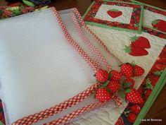 Protetor de mesa em filó com debrum de viés de algodão e decorado com moranguinhos de tecido. Pode ser com outros motivos, como pimentas, foto ao lado. R$ 25,00