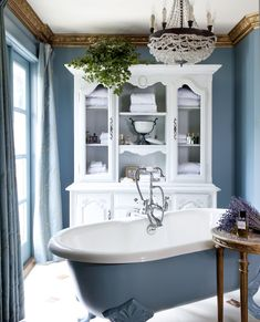 A 1920s iron and crystal chandelier from the south of France hangs above a freestanding tub in the Chateau-inspired bathroom.