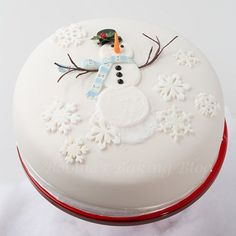 Delicious looking snowman inspired Christmas cake. The cake shows a huge snowman in the middle of the cake with a hat and scarf enjoying the snow.
