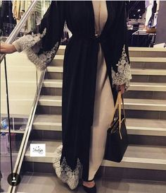 A beautiful black open abaya with with grey/white lace at the bottom and at the cuffs of the abaya. The simple white lace work adds sophistication . Arab Fashion, Islamic Fashion, Muslim Fashion, Modest Fashion, Fashion Dresses, Hijab Dress, Hijab Outfit, Modest Wear, Modest Outfits