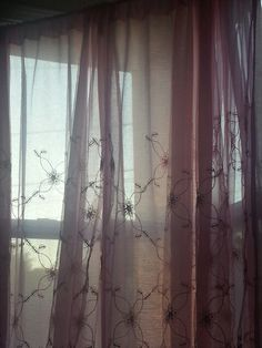 Sheer pink embroidered flower curtains.