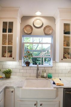 area above sink - wrapped tile around window well; window sill same material as counter-top; no soffit; glass doors on either side.