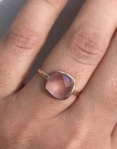 14k solid rose gold and genuine pink Quartz ring. The stone is 10mm by 10mm cushion checkerboard cut, genuine pink quartz, semi transparent, with some inclusions, 4 carats. Rings weight is 1.7g. Rings size is 7, I can resize free of charge (sizes 5-9). The band is 1.5mm thick. The stone is directly touching the skin (stone energy) The ring comes with a small velvet gift box.