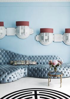 Tufted pale blue sofa with modern wall sconces