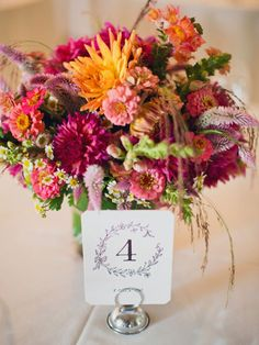 Ooh La!  dahlias, zinnias, snapdragons, wheat celosias, chamomile flowers, and ruby silk grass—all of which were in season for a September wedding :)