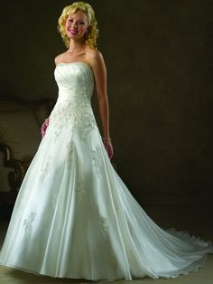 Modest wedding gown with a lace up back and adorned with beautiful lace accents