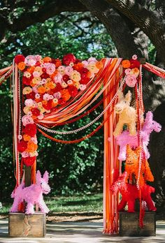 A colorful Dia de los Muertos-inspired ceremony arch with whimsical pinatas, paper blooms and festive ribbon streamers | Brides.com