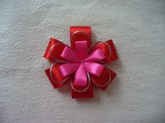 Dress up your little girl's hair with this pretty flower hair clip. Create a full bloom by combining several layers of flowers together.  This tutorial shows how easy it is to make this flower by incorporating both satin ribbon and ribbon cord to create layersfor a full bloom.  Be creative with your materials and color to create your own one-of-a-kind flower.    Materials   satin ribbon ribbon cord hair clip bead scissors needle and thread craft glue