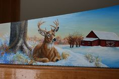 Winter farm, log cabin, barn, and white tail deer buck painting on a hand saw by sherrylpaintz.